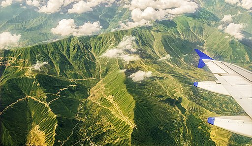 Aerial view of the green vegetation covered great Himalayas from the plane. Visible are the treacherous roads and the floating cumulus clouds.